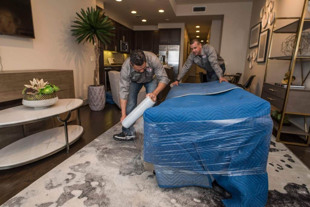 houston apartment movers carefully wrapping furniture in a market square apartment
